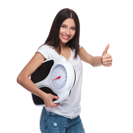 portrait of fit girl with scale making thumbs up sign while standing on white background