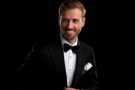 happy elegant man in tuxedo and bowtie looks to side away from the camera on black studio background