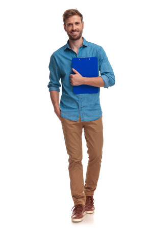 young casual student walks forward while holding notepad on white backround Stock Photo