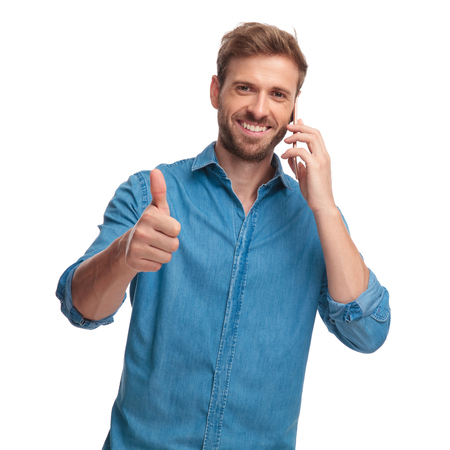 happy casual man talking on the phone makes the ok sign on white background Banque d'images