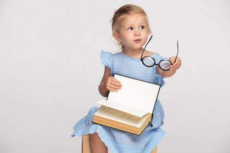 beautiful little girl holding her book and glasses while sitting on a chair on grey baclkground, pointing hand