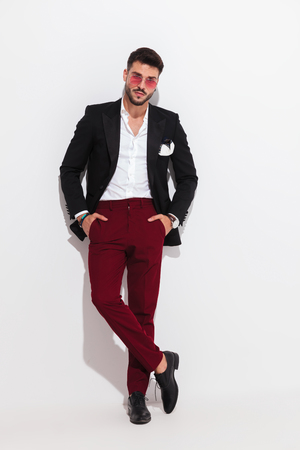 relaxed handsome man wearing black suit and red sunglasses