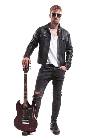 relaxed fashion man wearing black leather jacket and sunglasses posing with his electric guitar while standing on white background