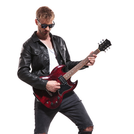 portrait of fashion man wearing leather jacket and sunglasses playing his electric guitar while standing on white background and looking down