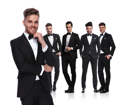 young group leader in tuxedo stands in front of his team on white background and smiles, looking pensive Stock Photo