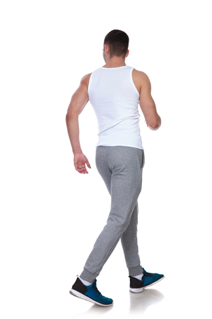 back view of fitness man walking on white background and looking to side