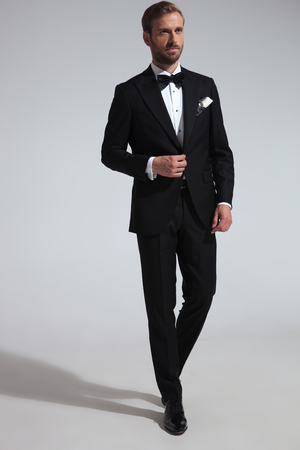 side view of an elegant man in tuxedo holding his button and walks on grey background