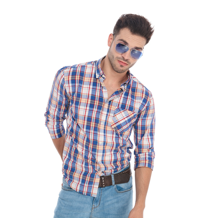portrait of sexy man wearing shirt with plaids and sunglasses while standing on white background 版權商用圖片