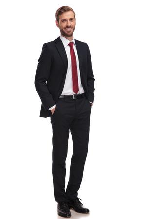Empresario relajado sonriendo y de pie con las manos en los bolsillos sobre fondo blanco.