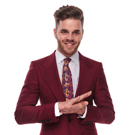 portrait of happy businessman wearing a grena colored suit rubbing his palms together and looking down to side while standing on white background 版權商用圖片