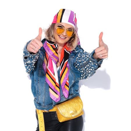 sexy woman wearing yellow sunglasses and colorful headscarf makes ok sign while standing on white background and smiling