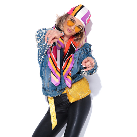 portrait of sexy casual woman in colorful clothes pointing fingers while leaning her head to side and winking Standard-Bild