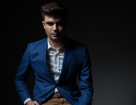 portrait of sexy smart casual man in blue suit sitting on dark grey background Stock Photo
