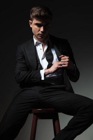 portrait of handsome groom pulling something from tuxedo pocket while sitting on wooden chair on grey background