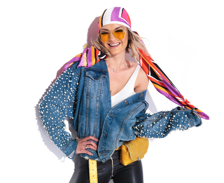 portrait of sexy blonde woman laughing while holding her colored headscarf and standing on white background with a hand on hip