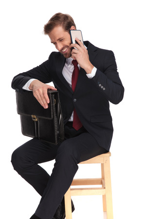 young businessman with suitcase sitting on a wooden chair and laughing while talking on the phone, on white background Фото со стока