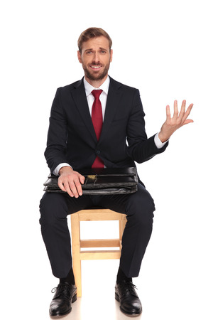 sarcastic businessman waiting for interview making an open hand gesture while sitting on white background, full body picture