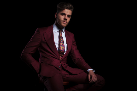 smugged young businessman sitting on a stool on black background Stock Photo