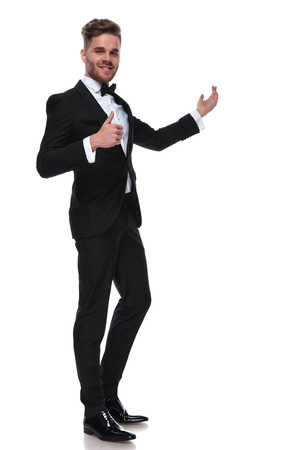 happy elegant man in tuxedo presenting and making the ok thumbs up hand sign on white background Stock Photo