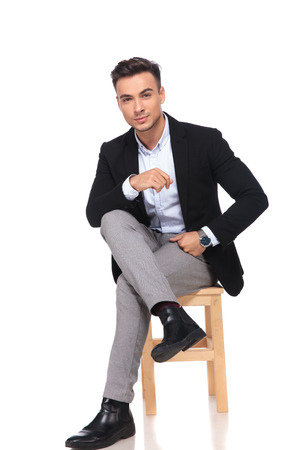 attractive businessman sitting on wooden chair with legs crossed on white background and resting his elbow on knee