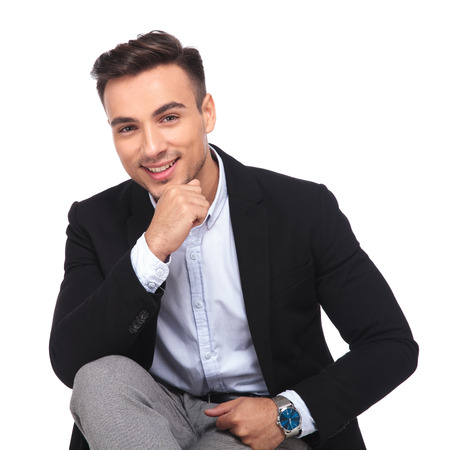portrait of pensive young businessman smiling and sitting on white background