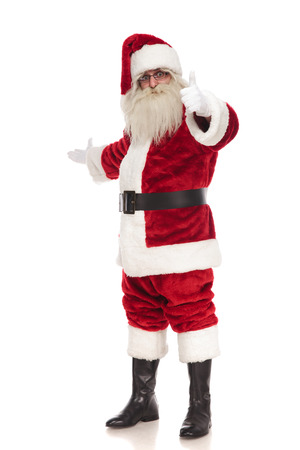 happy santa claus points finger and makes inviting gesture while standing on white background, full length picture