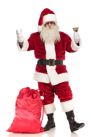 santa claus standing on white background with sack near his leg rings his bell and makes a welcoming gesture, full body picture