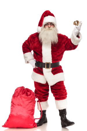 saint nick holding bell stands with hand on hip near presents bag on white background, full body picture