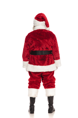 rear view of santa claus standing on white background and waiting in line, full body picture