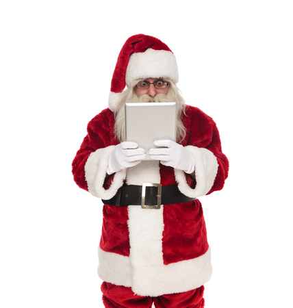 portrait of shocked santa looking at grey tablet while standing on white background