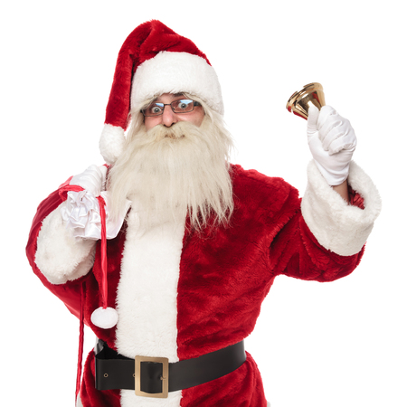portrait of old merry santa holding gifts bag and ringing bell while standing on white background
