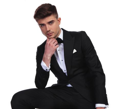 portrait of pensive groom in black tuxedo sitting on white background Stock Photo