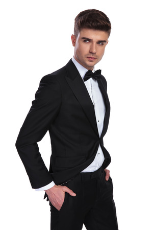portrait of relaxed classy man wearing a black tuxedo looking to side while standing on white background