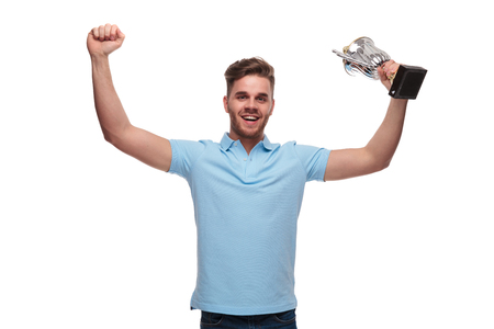 portrait of young man wearing blue polo shirt celebrating with trophy and hands in the air while standing on white background