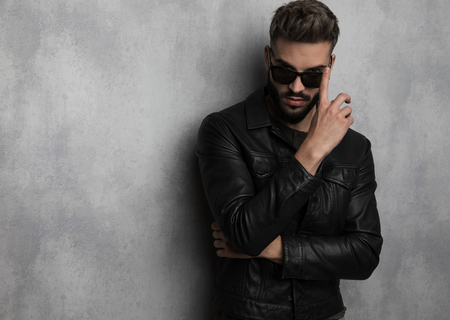 young man in leather jacket fixes his sunglasses while standing on grey background, portrait picture