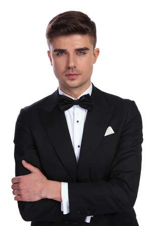 portrait of confident young groom in black tuxedo standing on white background with hands folded 免版税图像