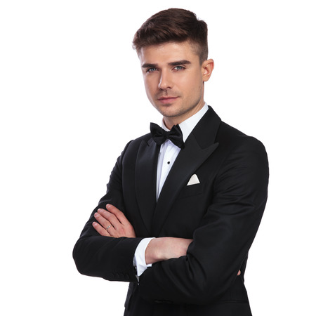 portrait of handsome elegant man standing with hands folded on white background Stock Photo