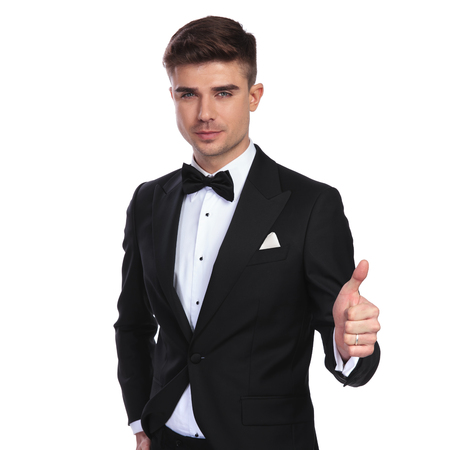 portrait of relaxed groom in black tuxedo making ok sign while standing on white background