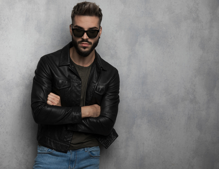 portrait of confident unshaved man wearing leather jacket and sunglasses leaning against a grey wallpaper background