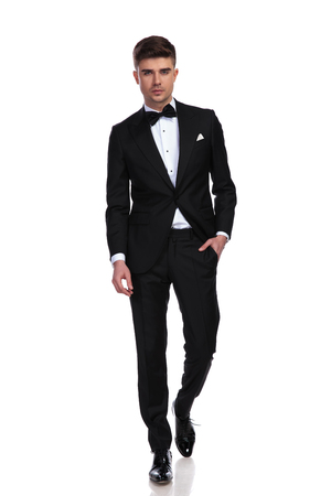 relaxed groom in black tuxedo walks forward with hand in pocket on white background Stock Photo