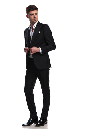 elegant man buttoning his black suit walks on white background and looks to side