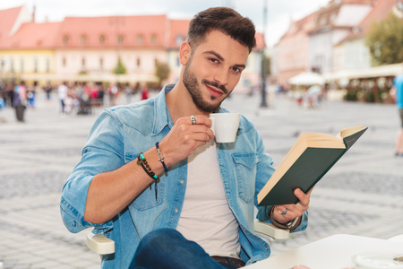 casual man drinks coffe and reads book in the city while sitting at a table, portrait picture Banco de Imagens