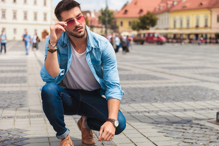 curious casual man crouching in the city fixes red sunglasses while looking to side, full length picture