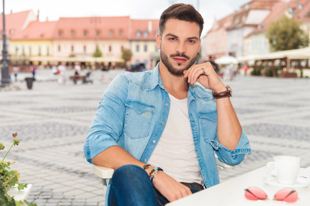 portrait of seated young casual man on urban background wearing rings and bracelets