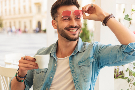 curious and smiling casual man fixing sunglasses drinks coffee while sitting at a table in the city and looking to side, portrait picture Stock fotó