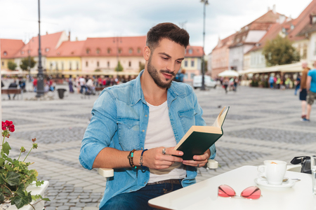 smiling casual man wearing denim shirt sitting at table and reading in the city, portrait picture