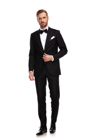 handsome businessman standing on white background and buttoning black suit