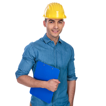portrait of relaxed engineer wearing hard cap and holding papers while standing on white background with hand in pocket