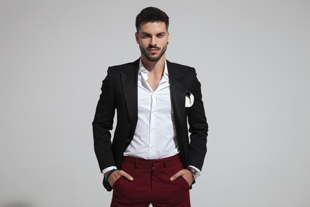 portrait of relaxed fashion man wearing black suit and red pants holding pockets while standing on light grey background Standard-Bild - 115691424