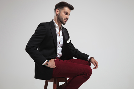 side view of seated smart casual man wearing black suit and red pants looking down on light grey background, portrait picture